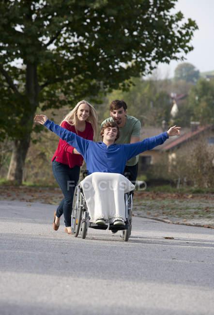 Coppia giovane con amico seduto in sedia a rotelle — Foto stock