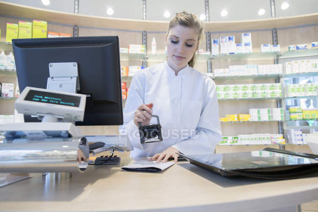Young pharmacist in pharmacy stamping prescription — Stock Photo