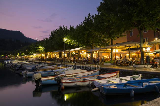 Italy, Veneto, Garda, Lake Garda, lakeside promenade with restaurants and boats in the evening — Stock Photo