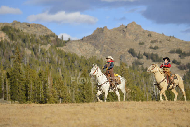 USA, Wyoming, two young cowboys riding — Stock Photo