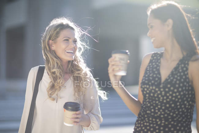 Two happy women with coffee to go cups — Stock Photo