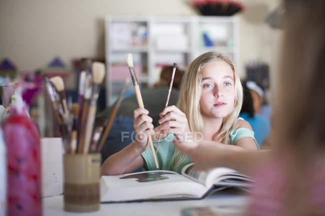 Дівчина в мистецтв класу проведення пензлі — стокове фото