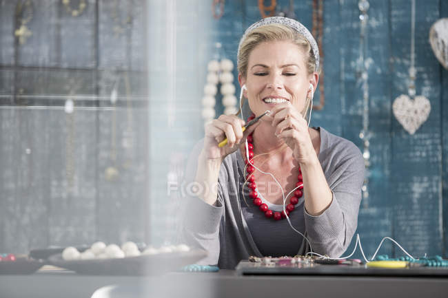 Woman working with pliers while listening to music on her earphone — Stock Photo