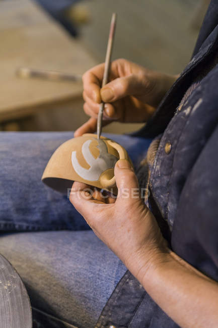 Поттер в мастерской рисует чашу — стоковое фото
