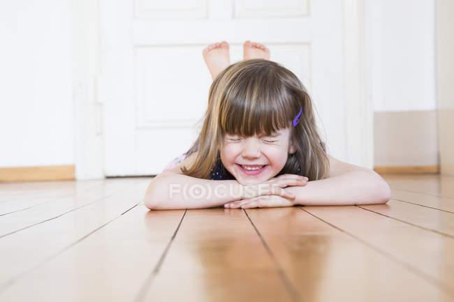 Улыбающаяся девушка лежит на деревянном полу и закрывает глаза. — стоковое фото