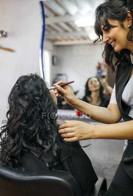 Female visagiste styling female customer in front of mirror — Stock Photo