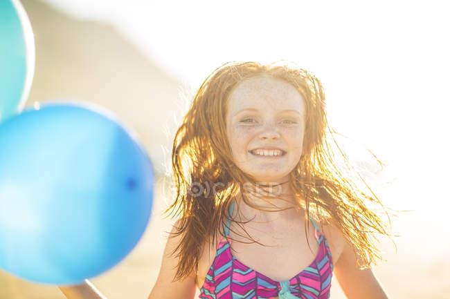 Menina na praia sorrindo e segurando balões — Fotografia de Stock