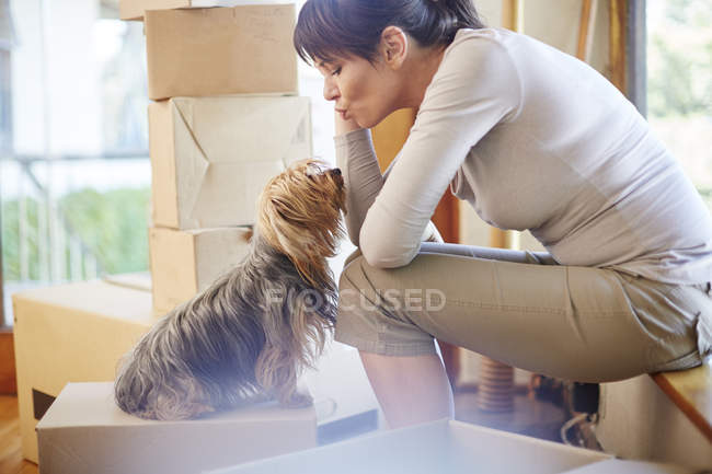 Woman moving house sharing a moment with the dog — Stock Photo