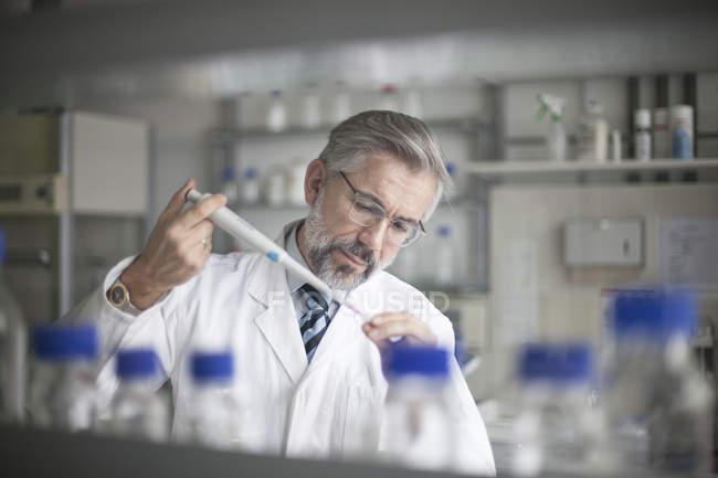 Ученый наливает жидкость в пробирку — стоковое фото