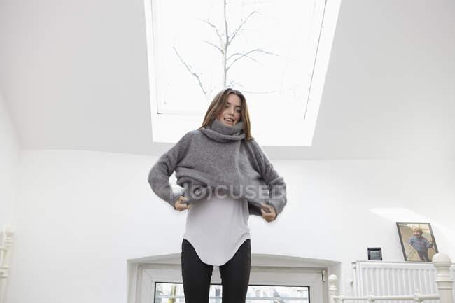 Женщина в спальне, положив на пуловер — стоковое фото