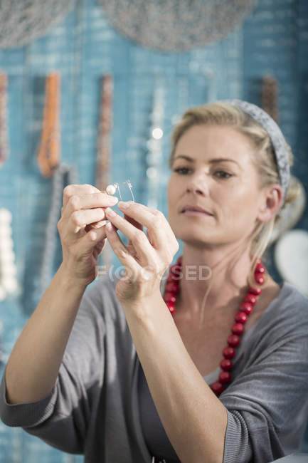 Woman working with wire to create a bead necklace — Stock Photo