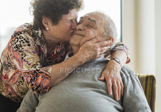 Senior woman hugging and kissing his husband — Stock Photo