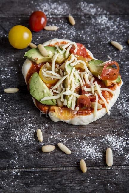 Авокадо помидор сырые пицца на темной древесины — стоковое фото