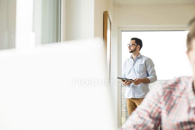 Junger Mann steht mit digitalem Tablet am Fenster — Stockfoto