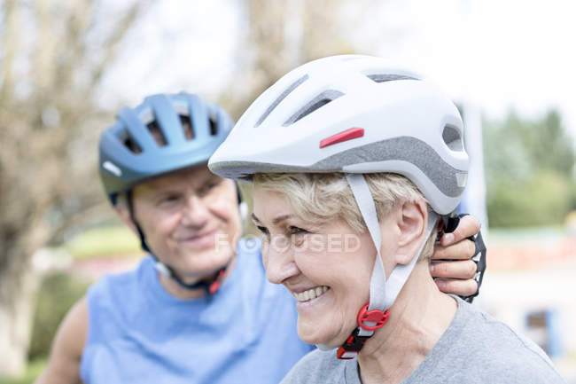 Portrait of smiling senior woman with cycling helmet in front of her husband — Stock Photo