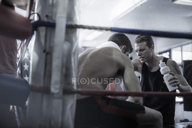 Boxer having a break with trainer in corner of the boxing ring — Stock Photo