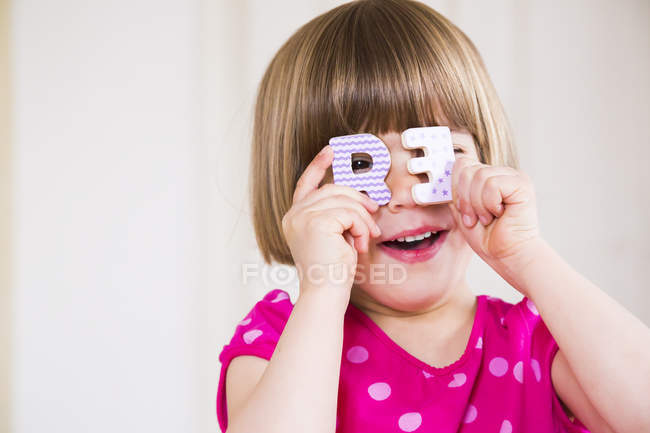 Portrait of smiling little girl peeking through two wooden letters — Stock Photo