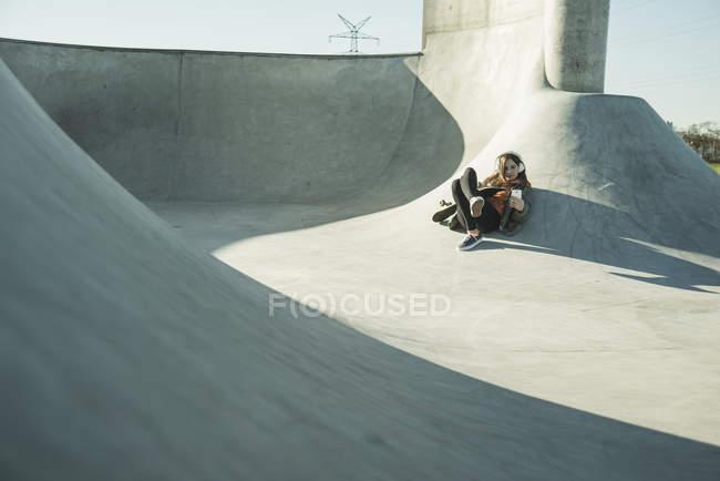 Fille avec téléphone cellulaire et un casque en skatepark — Photo de stock