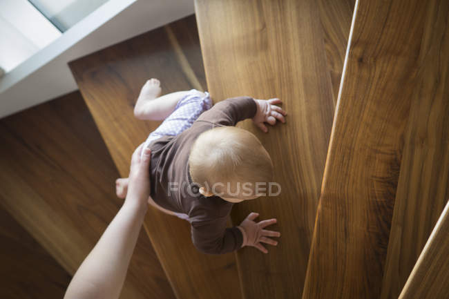 Female hand helping baby girl climbing up a stairs — Stock Photo