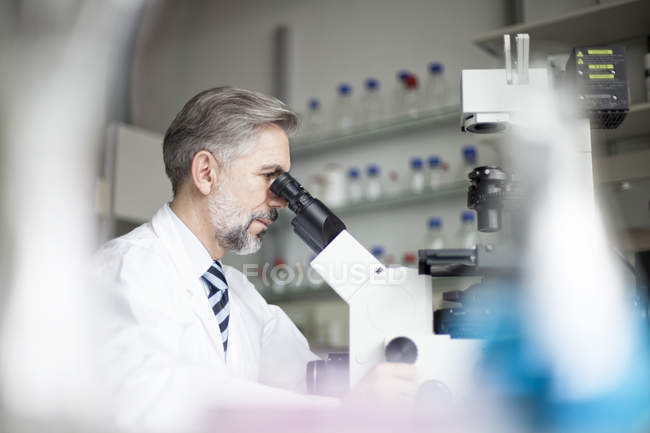 Scientifique en laboratoire regardant au microscope — Photo de stock