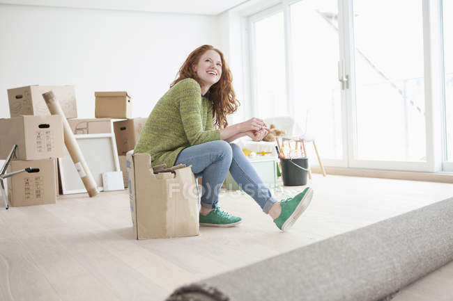 Young woman in new flat sitting on cardboard box — Stock Photo