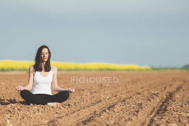 Woman meditating on a field — Stock Photo