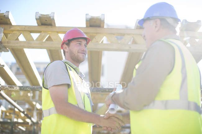 Two construction workers shaking hands in construction site — Stock Photo