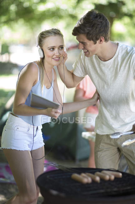 Young couple on holiday grilling sausages and listening to music on a digital tablet — Stock Photo