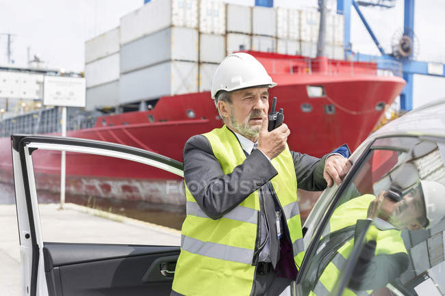 Man with walkie-talkie wearing protective clothing at container port — Stock Photo