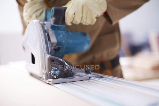 Close-up of Carpenter sawing wood in workshop — Stock Photo