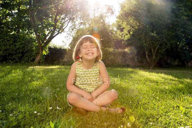 Little girl wearing cherries sitting on a meadow at backlight — Stock Photo