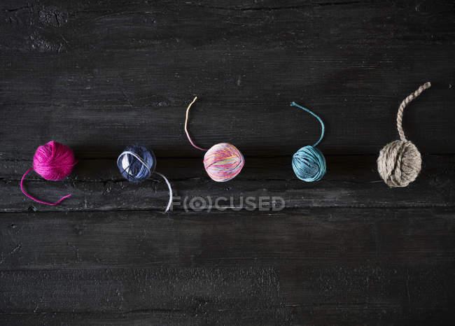 Reihe von fünf verschiedenen Wollknäueln auf schwarzem Holz — Stockfoto