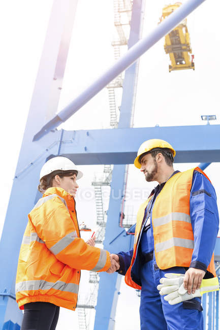 Man and woman wearing protective clothing shaking hands at container port — Stock Photo