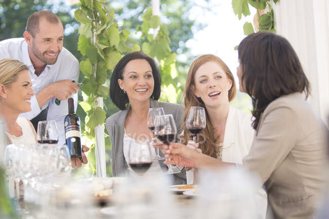 Официант, представляя бутылка красного вина для женщин на сессии дегустации вина — стоковое фото