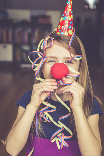 Little girl with clown nose and cap blowing streamer — Stock Photo