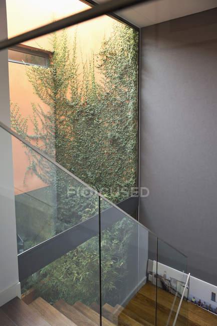 Escalera con barandilla de cristal en una casa de una familia moderna - foto de stock