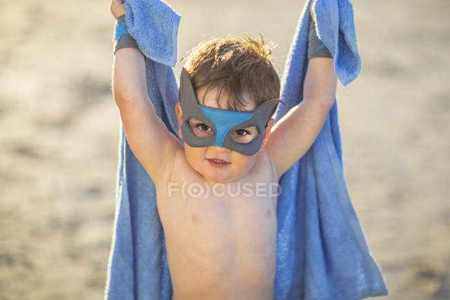 Little boy on the beach dressed up as a superhero with mask and towel — Stock Photo