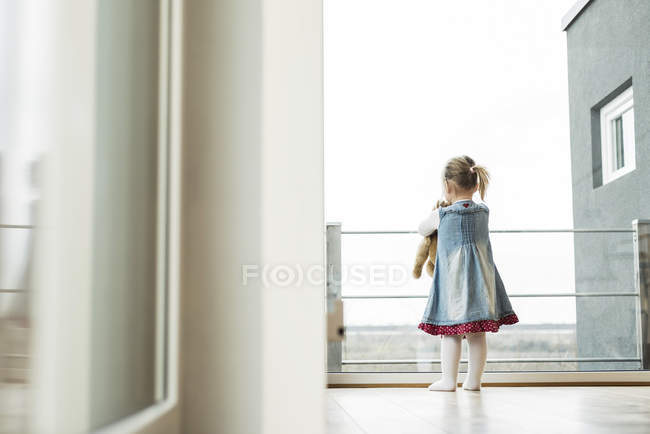 Girl holding teddy looking out of window — Stock Photo