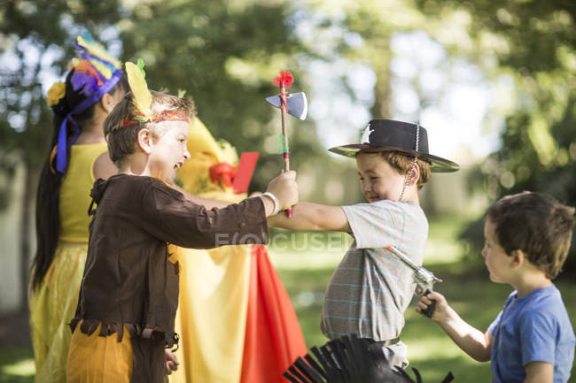 Kids in garden playing Cowboys and Indians — Stock Photo