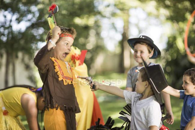 Дети в саду играют в ковбоев и индейцев — стоковое фото
