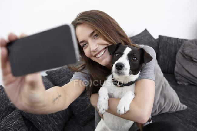 Молода жінка, беручи selfie з собакою — стокове фото