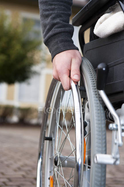 Рука молодого человека на говорил о коляске — стоковое фото