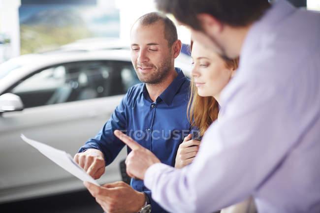 Couple at car dealer buying new car — Stock Photo