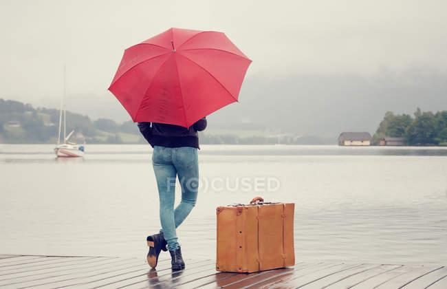 Autriche, Mondsee, adolescente avec parapluie rouge debout sous la pluie avec valise — Photo de stock