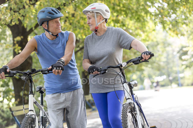 Senior couple with cycling helmets and bicycles — Stock Photo