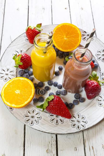 Апельсиновый и клубничный смузи в стеклянных бутылках и фруктах на блюдечке — стоковое фото