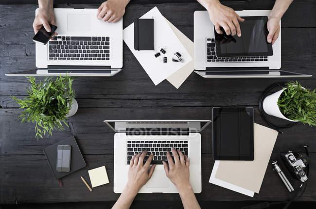 Mani umane che lavorano in ufficio con laptop, smartphone e tablet digitale — Foto stock