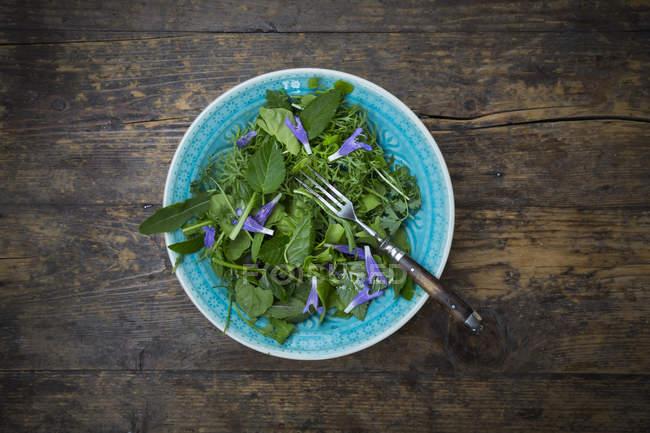 Чаша дикі трави салат з харчову квіти на темного дерева — стокове фото