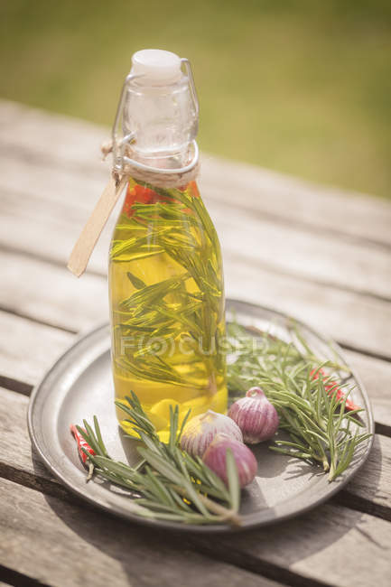 Rosemary oil in bottle, garlic, rosmary and chilli peppers on plate — Stock Photo