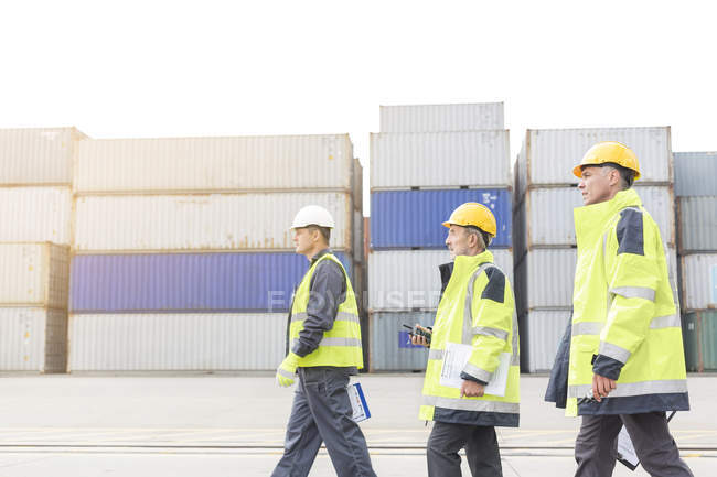 Three men wearing protective clothing walking at container port — Stock Photo